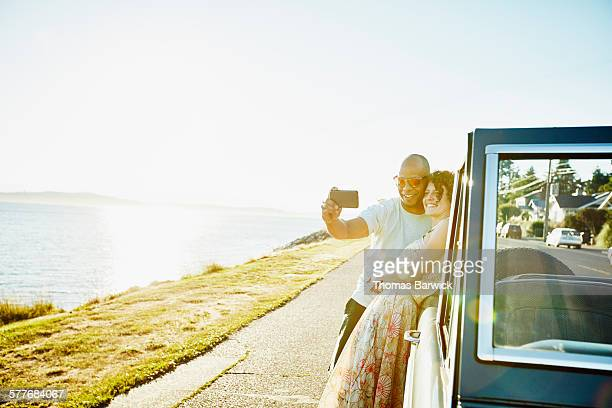 Couple leaning on convertible taking selfie