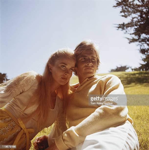 Couple leaning on grass