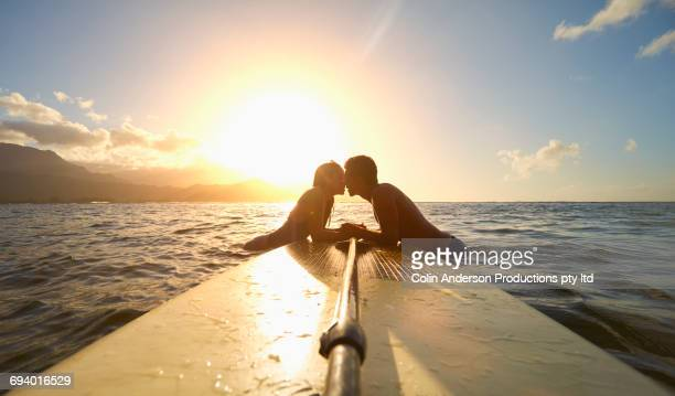 Couple leaning on paddleboard in ocean kissing at sunset