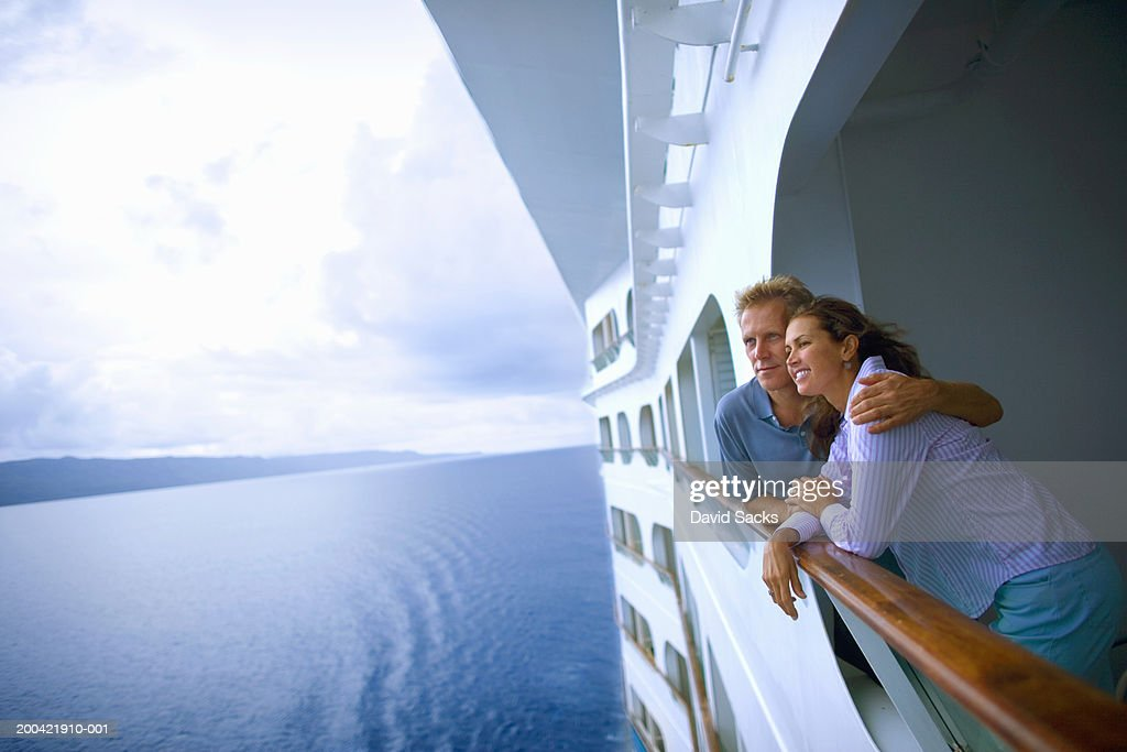 Couple leaning on rail of cruise ship, looking at ocean : Stock-Foto