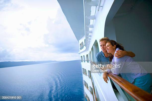 couple leaning on rail of cruise ship, looking at ocean - ponte di una nave foto e immagini stock