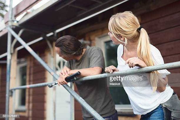 Couple leaning on scaffolding outside house during home improvement