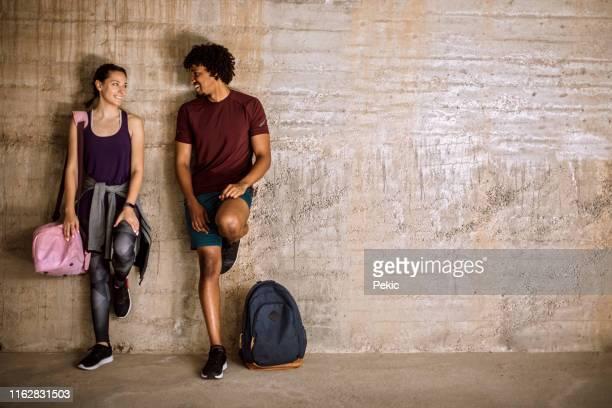 ワークアウト後に壁に寄りかかっているカップル - スポーツバッグ ストックフォトと画像