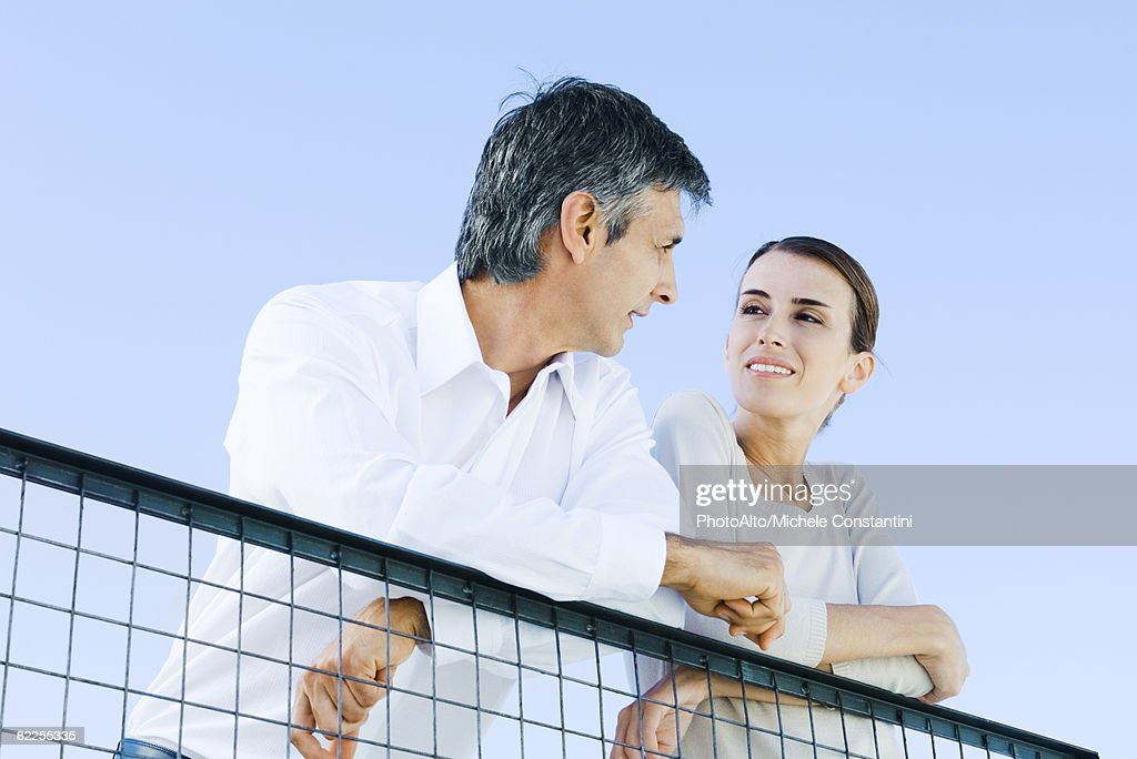 Couple leaning on wire fence, smiling at each other, low angle view : Stock Photo