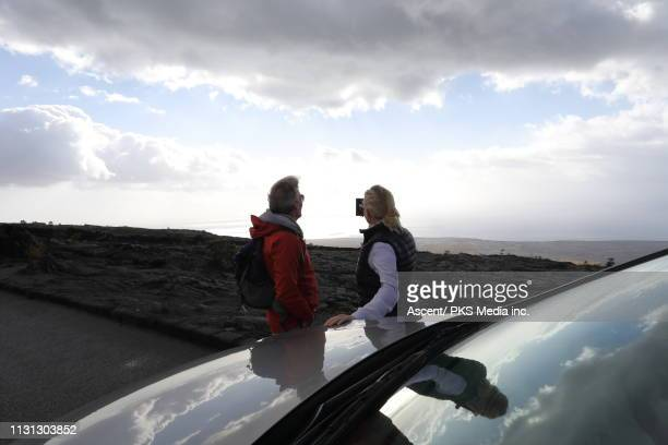 Couple leans against car and looks towards ocean and sunlit clouds