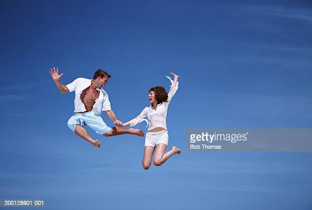 Couple leaping in the air, holding hands, low angle view