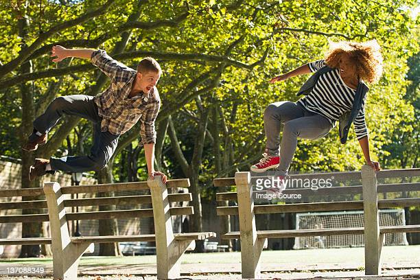 Couple leaping over park benches