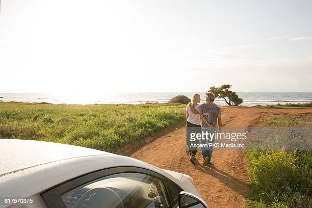 Couple leave car, walk along rural road to sea