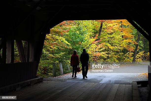 couple leave covered bridge with trees in autumn - covered bridge stock pictures, royalty-free photos & images