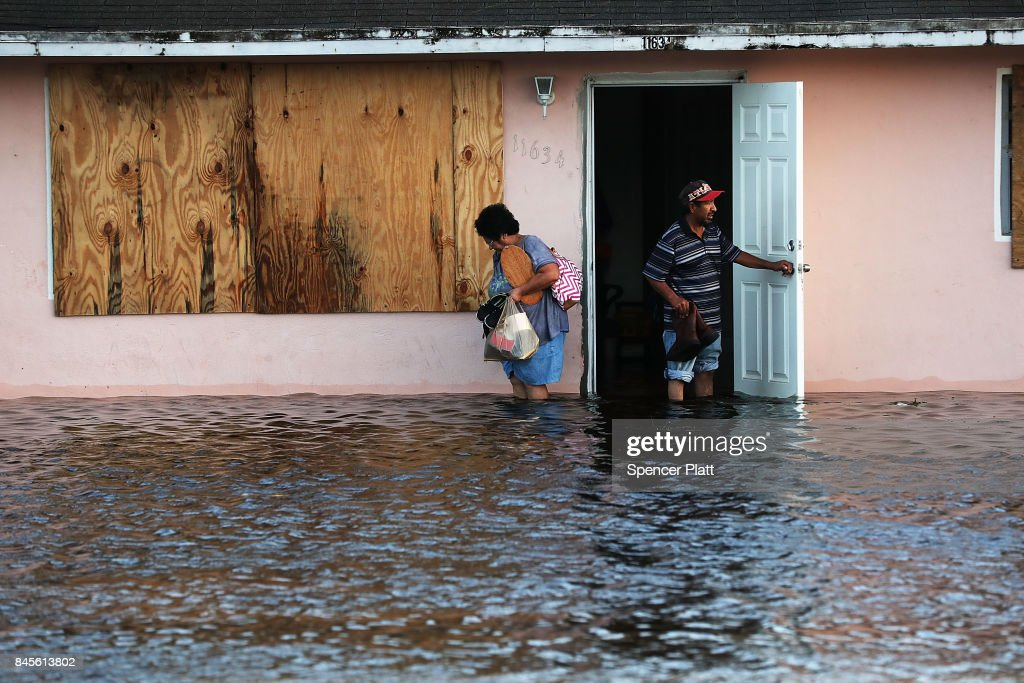 A couple leave their flooded home the morning after Hurricane Irma swept through the area on September 11, 2017 in Bonita Springs, Florida. Hurricane Irma made another landfall near Naples yesterday after inundating the Florida Keys. Electricity was out in much of the region with localized flooding.