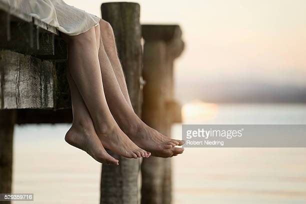 Couple legs dangling on pier, Bavaria, Germany