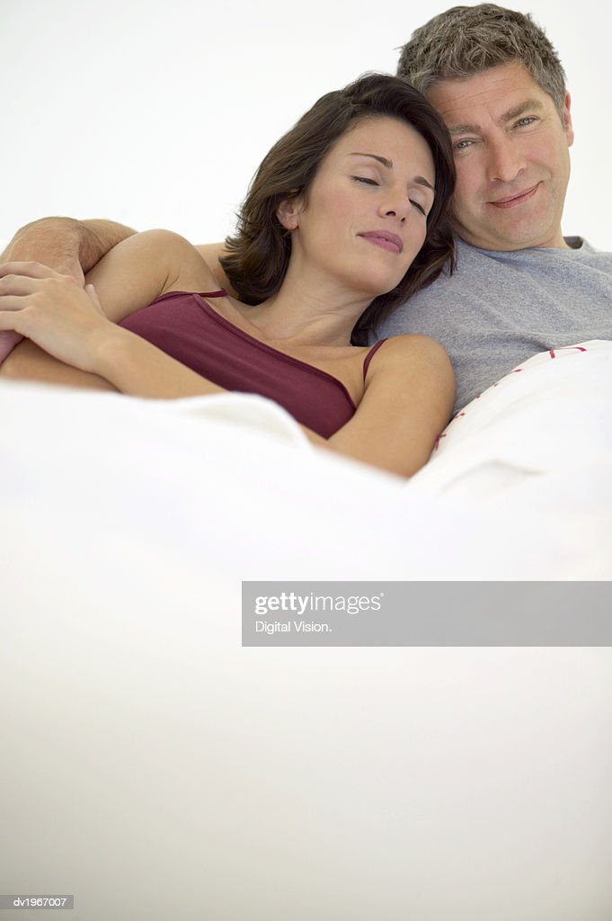 Couple Lie in Bed, the Man With His Arm Around the Sleeping Woman : Stock Photo