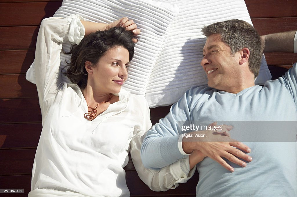 Couple Lie Side by Side on Decking and Gaze Contentedly at Each Other : Stock Photo