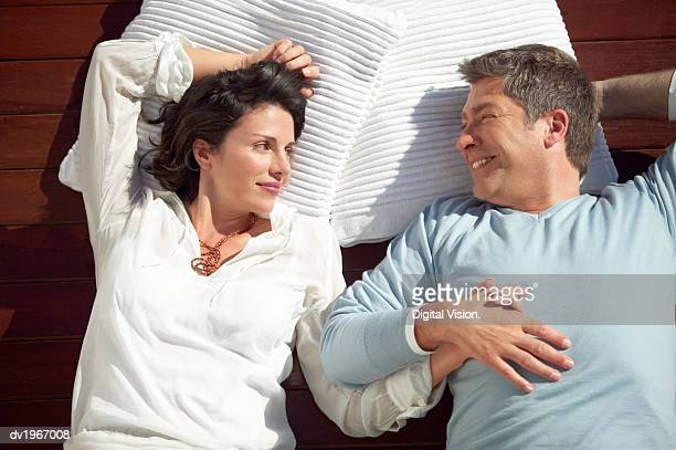 couple lie side by side on decking and gaze contentedly at each other - looking down her blouse stock photos and pictures