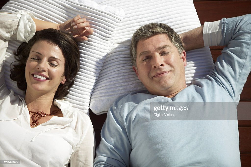 Couple Lie Side by Side on Towels, Sunbathing With Their Eyes Closed : Stock Photo