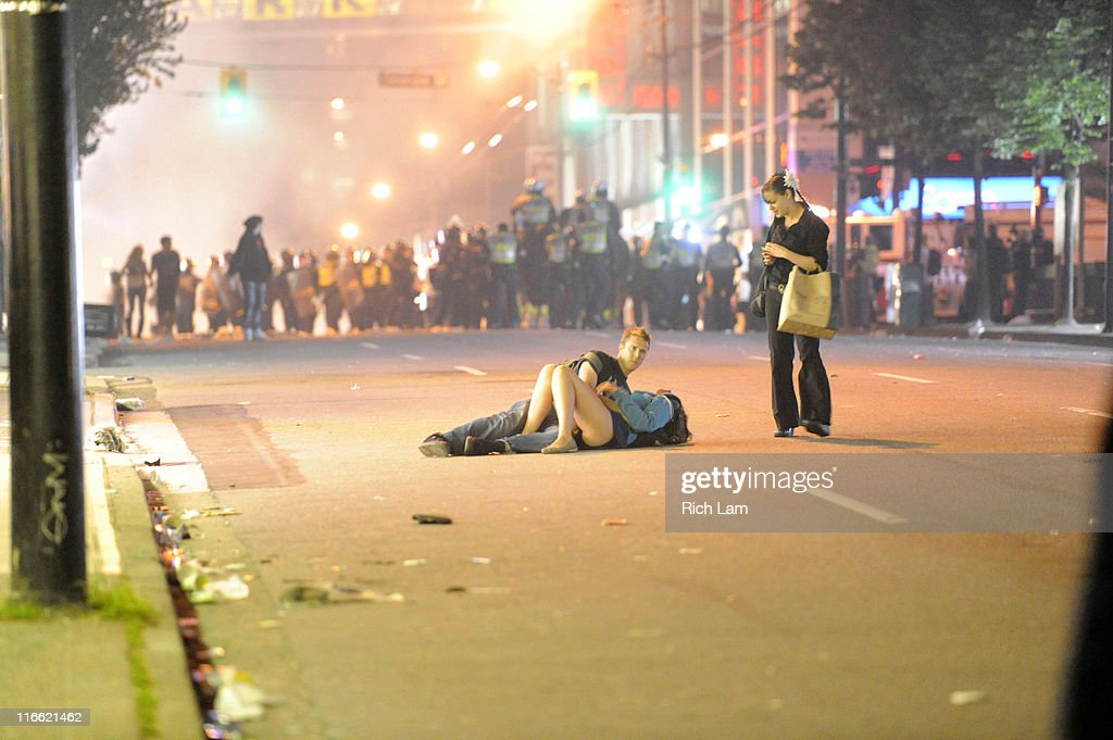 A couple lies on a street as an unidentified woman approaches on June 15, 2011 in Vancouver, Canada. Vancouver broke out in riots after their hockey team the Vancouver Canucks lost in Game Seven of the Stanley Cup Finals.