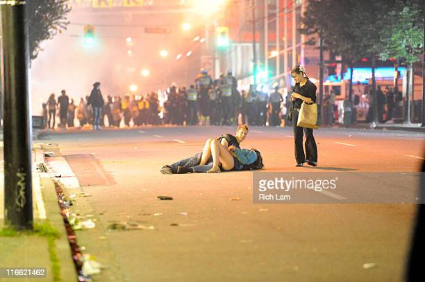 A couple lies on a street as an unidentified woman approaches on June 15 2011 in Vancouver Canada Vancouver broke out in riots after their hockey...