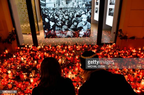 TOPSHOT A couple light a candle at a memorial to commemorate the 29th anniversary of the socalled Velvet Revolution on November 17 2018 in Prague The...