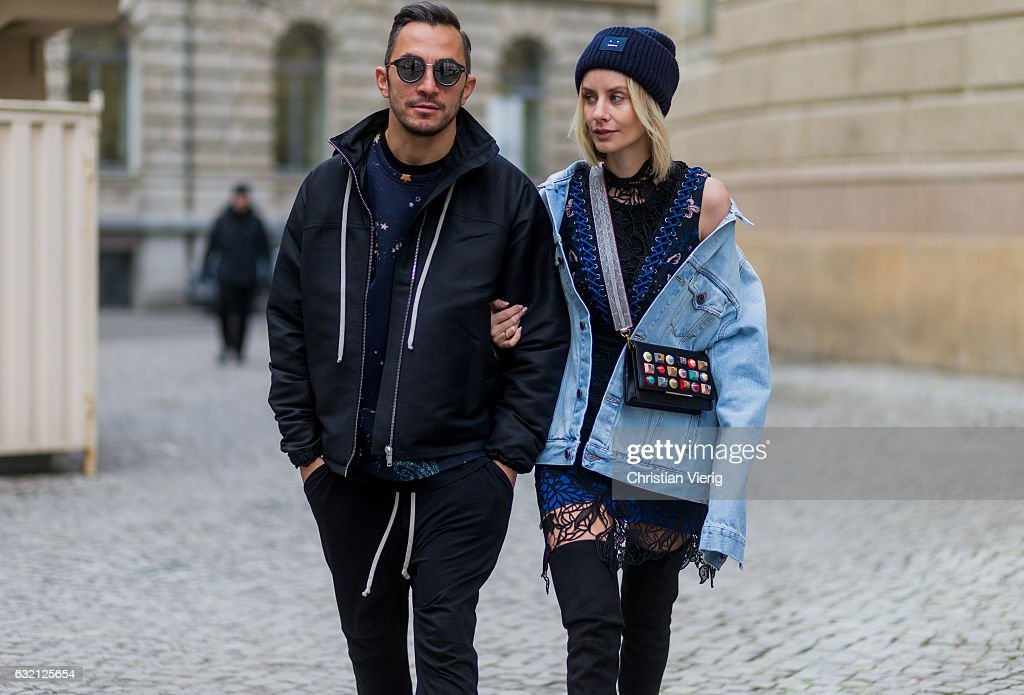 Couple Lisa Hahnbueck wearing Off White Printed Denim Jacket Men Section, Self-Portrait Embroidered Dress with Lacing, Over knee Boots Stuart Weitzman Style Alllegs, Acne Studios Beanie, Fendi Clutch with colored Studs with MCM Phython strap and Dima: RICK OWENS Zipped Jacket, Valentino Cosmo Printed sweatshirt, Rick Owens Cotton harem pants, Adidas NMD R1 sneaker, Dior Magnitude Sunglasses during the Mercedes-Benz Fashion Week Berlin A/W 2017 at Kaufhaus Jandorf on January 19, 2017 in Berlin, Germany.