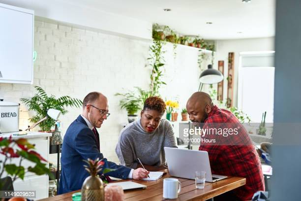 couple listening to financial advisor at home with laptop - planning stock pictures, royalty-free photos & images