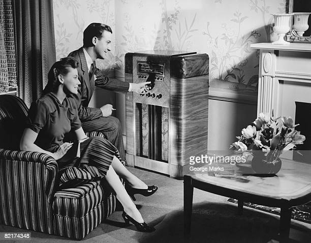 Couple listening to radio in living room, (B&W)