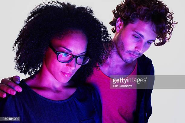 Couple lit by digital device.