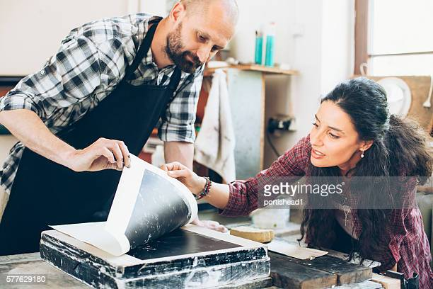 Couple lithograph workers creating new pattern at printing house