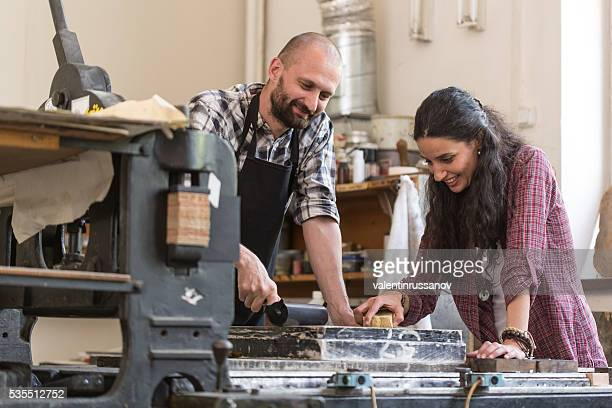 couple lithography workers using printing press at workshop - engraved image stock pictures, royalty-free photos & images