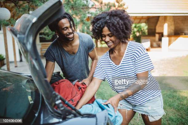 couple loading a car. - black boot stock pictures, royalty-free photos & images