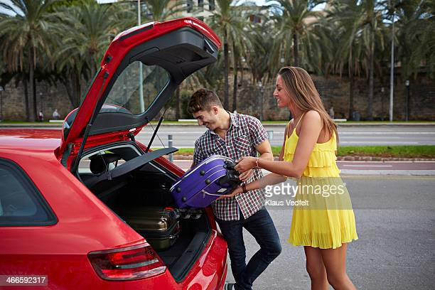 couple loading back of car with suitcases - klaus vedfelt mallorca stock pictures, royalty-free photos & images