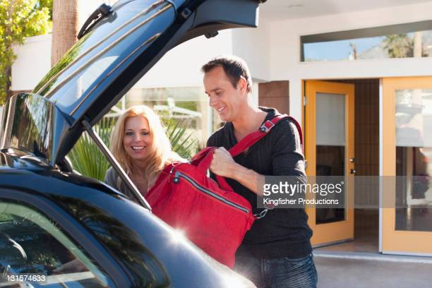 Couple loading bags into car