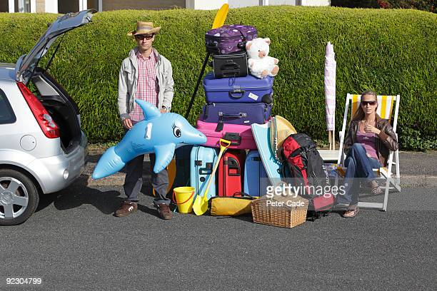 couple loading car for holiday - excess stock pictures, royalty-free photos & images