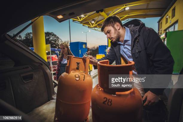 couple loading lpg gas bottles in trunk at the gas station - gas tank stock photos and pictures