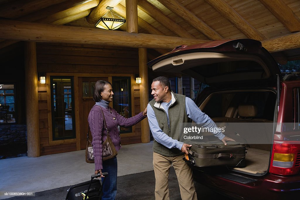 Couple loading luggage into car outside hotel : Foto stock