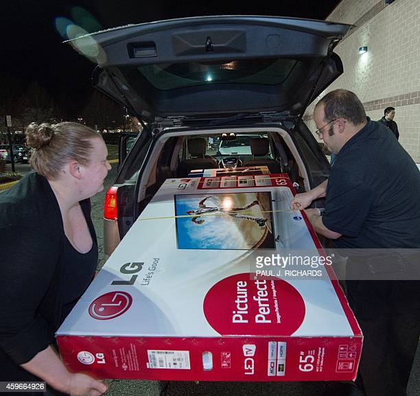 A couple loads their newly purchased 65' screen TV into their van outside the Best Buy during the Black Friday doorbuster sale that started on...