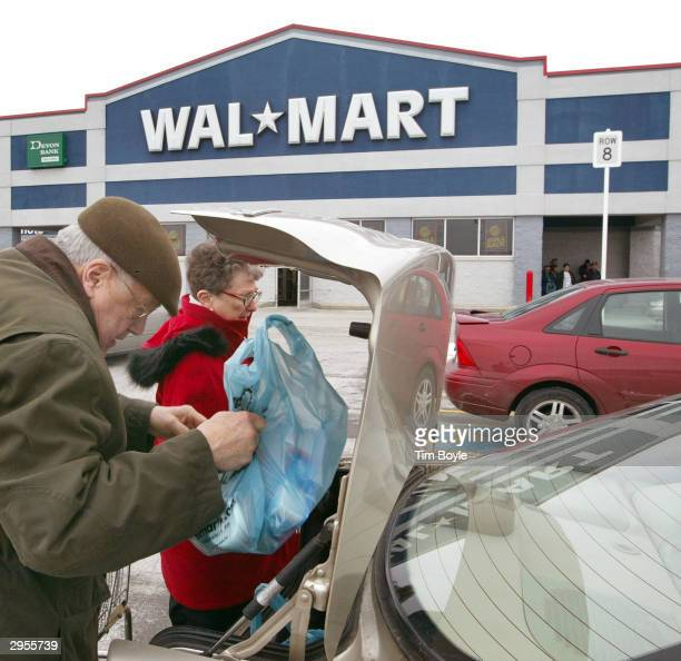 A couple loads their purchases into their car's trunk outside a WalMart store February 9 2004 in Niles Illinois WalMart may be entering a deal with...