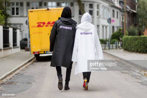 Couple look a like holding arms in front of a DHL van - Model and Blogger Alexandra Lapp wearing oversized raincoat with a hood in white from...