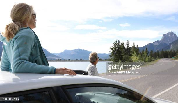 Couple look across mountain scene from car