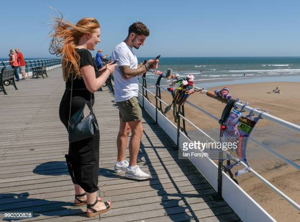 A couple look at a display of knitting attached to railings on the pier after a secretive group of knitters left their latest display as a...