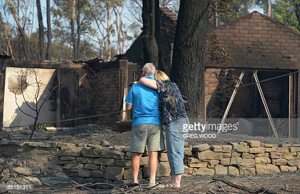 A couple look at a house burnt out by bushfires in Winmalee in Sydney's Blue Mountains on October 18 2013 Residents faced scenes of devastation on...