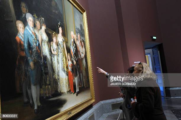A couple look at a painting by Spanish artist Francisco Goya titled 'The family of Charles IV' on show at the Prado museum as part of a new...