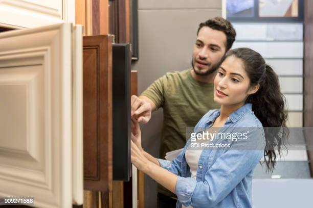 couple look at cabinet samples in hardware store - home improvement stock pictures, royalty-free photos & images