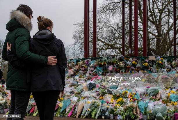 Couple look at floral tributes left at Clapham Common bandstand where people continue to pay their respects to Sarah Everard on March 16, 2021 in...