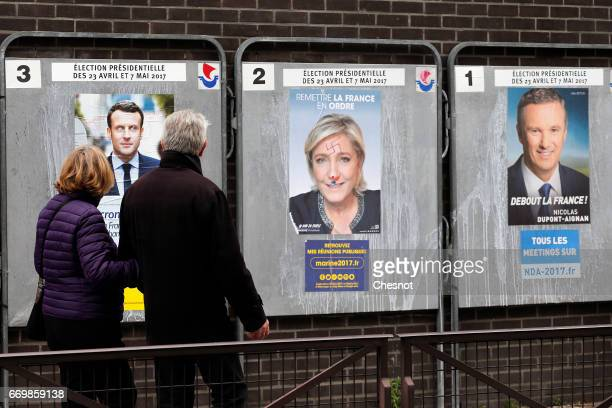 A couple look at graffitied official campaign posters of Marine Le Pen French National Front and political party leader Emmanuel Macron head of the...