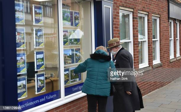 Couple look at houses for sale at an estate agents in Market Town of Leek on November 11, 2020 in Leek, England. The United Kingdom will continue to...