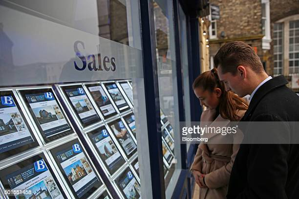 A couple look at houses for sale in the window of Balgores estate agents in this arranged photograph in Chelmsford UK on Tuesday Dec 15 2015 UK...