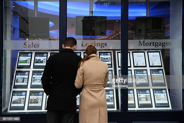 A couple look at houses for sale in the window of Balgores estate agents in Chelmsford UK on Tuesday Dec 15 2015 UK asking prices rose an annual 74...