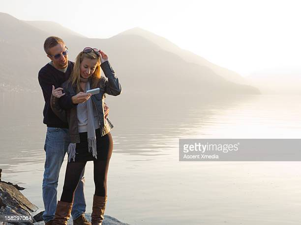 couple look at picture on cell phone, at lake edge - ascona stock pictures, royalty-free photos & images