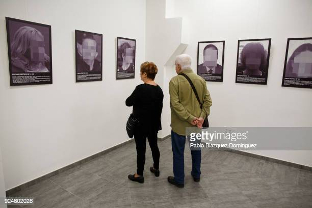 A couple look at pictures including one depicting jailed Catalan leader Oriol Junqueras during the presentation of Spanish artist Santiago Sierra's...