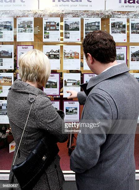 A couple look at residential properties for sale on display in an estate agents window in Hornchurch Essex UK on Thursday Dec 6 2007 The Bank of...
